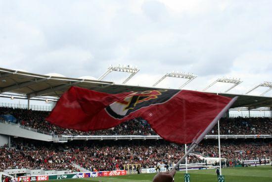 photographie d'un drapeau toulousain avec l'écusson, le logo, agité par un supporter